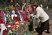"""Moscow, Russia, 26/04/2007..Russians visit Boris Yeltsin's grave to pay their last respects after Novodevichy Cemetery was  reopened to the public on the day following the former Russian President's funeral. A woman carrying a bag with the words """"be free"""" lays flowers on the grave.."""