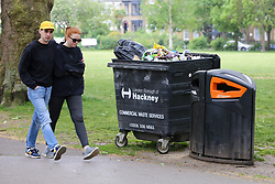 © Licensed to London News Pictures. 10/05/2020. London, UK. A couple walk past an overflowing bin in London Fields park in Hackney, north London today, following a tweet from local police reporting that hundreds of people were having pizzas, beers and wine on the hottest day of the year so far during lockdown on Saturday 9 May. Later today, Prime Minister Boris Johnson is set to announce measures to ease the coronavirus lockdown, which was introduced on 23 March to slow the spread of the COVID-19. Photo credit: Dinendra Haria/LNP