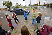 From 2008. Lois Arkin, founder of LA Eco-Village, engages in driver re-education. By forcing them around people in circle, drivers become aware of sharing street use. Founded in 1993, LA Eco-Village demonstrates the processes for creating a healthy neighborhood ecologically, socially and economically and to reduce environmental impacts while raising the quality of neighborhood life.