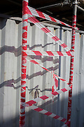 Red and white striped tape covers scaffolding on a south London construction site.