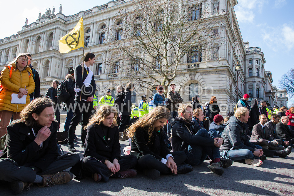 London, UK. 9th March, 2019. Climate activists from Extinction Rebellion sit in the road in Whitehall after pouring artificial blood on the ground outside Downing Street as part of an act of civil disobedience named 'The Blood of Our Children' to call on the Government to take immediate steps to combat the current climate and ecological emergency.