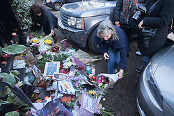 Highgate, London, December 26th 2016. Fans gather outside the London home of pop icon George Michael who died on Christmas day. PICTURED: A woman places flowers outside the gate.