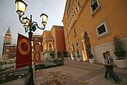 A couple walks pass the Venetian casino in Macau, China, on February 21, 2008. The Venetian Macao-Resort-Hotel is a 163,000 square foot casino featuring 405 slots and 277 table games. Macao has overtaken Las Vegas with a gambling revenue of 7 billion U.S. dollars in 2006 (Las Vegas' was 6.6 billion U.S. dollars), and is now the world's top casino hut. Photo by Lucas Schifres/Pictobank