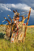 Shoshone Native American in a traditional Sneak Up Dance against a stormy Wyoming sky photographed by Mike Jackson