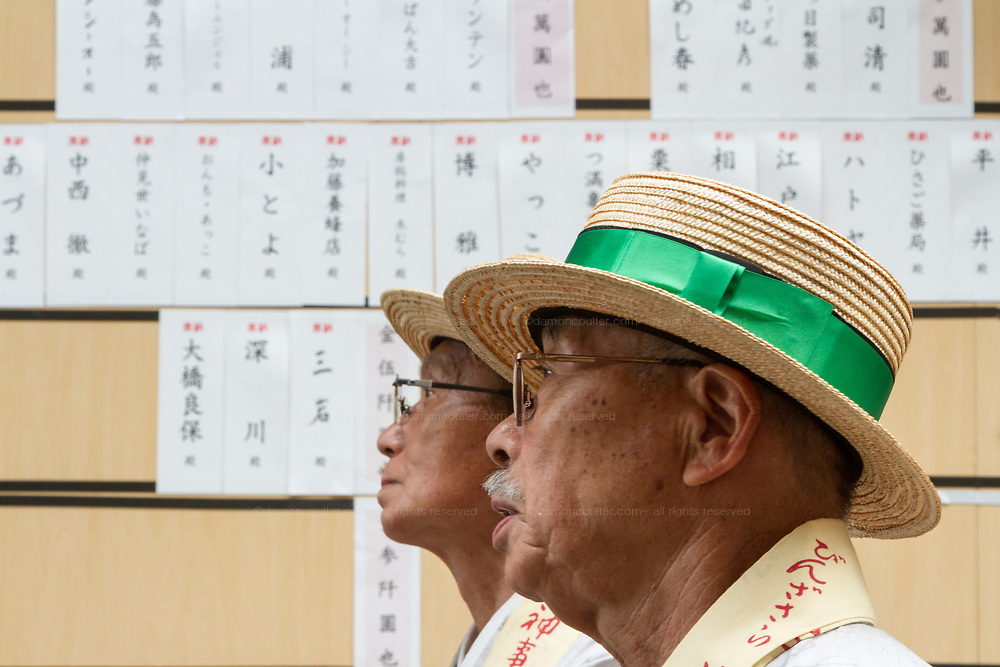 Men wearing kimono and straw boater hats  take part in the Daigyoretsu or Grand on  first day of the three-day Sanja Matsuri, Asakusa, Tokyo, Japan. Friday May 18th 2018. The Sanja matsuri, or festival, takes place over the third weekend of May in the streets around the famous Senso-ji Temple. It lis one of the biggest festivals in Japan and lasts for three days  (May 18th to May 20th) with parades of large mikoshi, or portable shrines, carried around the streets by crowds of supporters