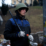 KIEV, UKRAINE - February 23, 2014: A member of Maidan's defence unit is seen holding a flower while taking guard at one of the many checkpoints outside Kiev's Independence Square. CREDIT: Paulo Nunes dos Santos