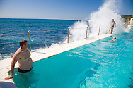 The Icebergs Swim Club swimming during off season with other community swimming club members at the historic Bondi Baths, a saltwater swimming pool.  Here waves crash into the side of the pool.