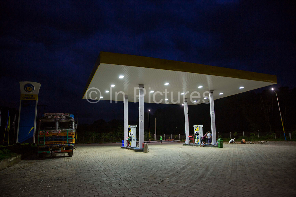A colorful truck parked in an empty petrol station at night Nongpoh, Ri-Bhoi district on 20th September 2018 in Meghalaya, India. Some people rest at a pump while some other people lay a new brick floor.