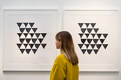 "© Licensed to London News Pictures. 21/01/2020. LONDON, UK. A staff member views works in the series ""Bagatelle 3"", 2015, by Bridget Riley. Preview of London Art Fair at the Business Design Centre in Islington.  Over 100 galleries are offering works, including museum-quality modern and contemporary art from internationally renowned artists and emerging artist, to collectors in a show which runs 22-26 January 2020.  Photo credit: Stephen Chung/LNP"