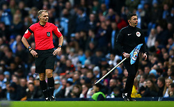 Referee Graham Scott (left) looks on as the broken corner flag is replacedduring the FA Cup fourth round match at Etihad Stadium, Manchester.