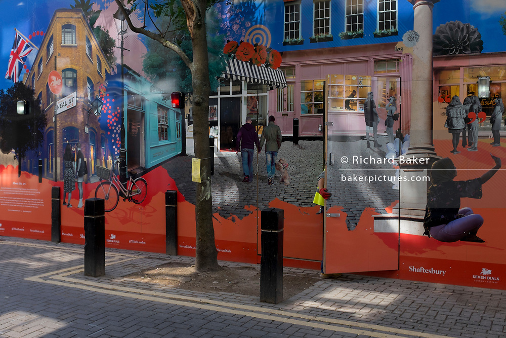 The hand of a construction street workman closes the door leading into the site hoarding of a new retail business, featuring everyday life in the Neal Street and Seven Dials area of the West End, on 2nd July 2020, in London, England.