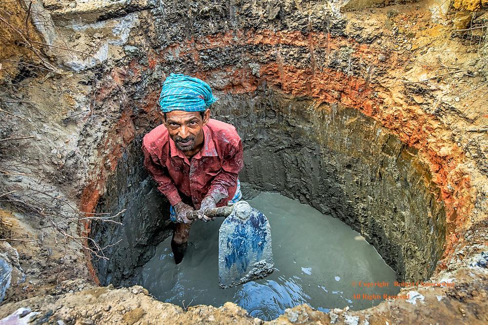 Circular Work: A man splattered in mud, looks up from digging his circular, water filled hole, Dhaka Bangladesh.