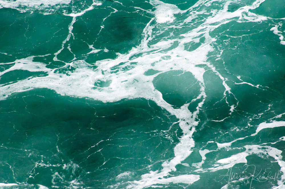 Abstract aquamarine waves swell in the surf zone of Big Sur, as the shadow of kelp forests swirl below<br />