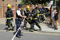 © Licensed to London News Pictures. 14/06/2017. London, UK. Firefighters on scene as the Grenfell Tower fire still is not under control 14 hours after the fire broke in west London on 14 June 2017. Photo credit: Tolga Akmen/LNP