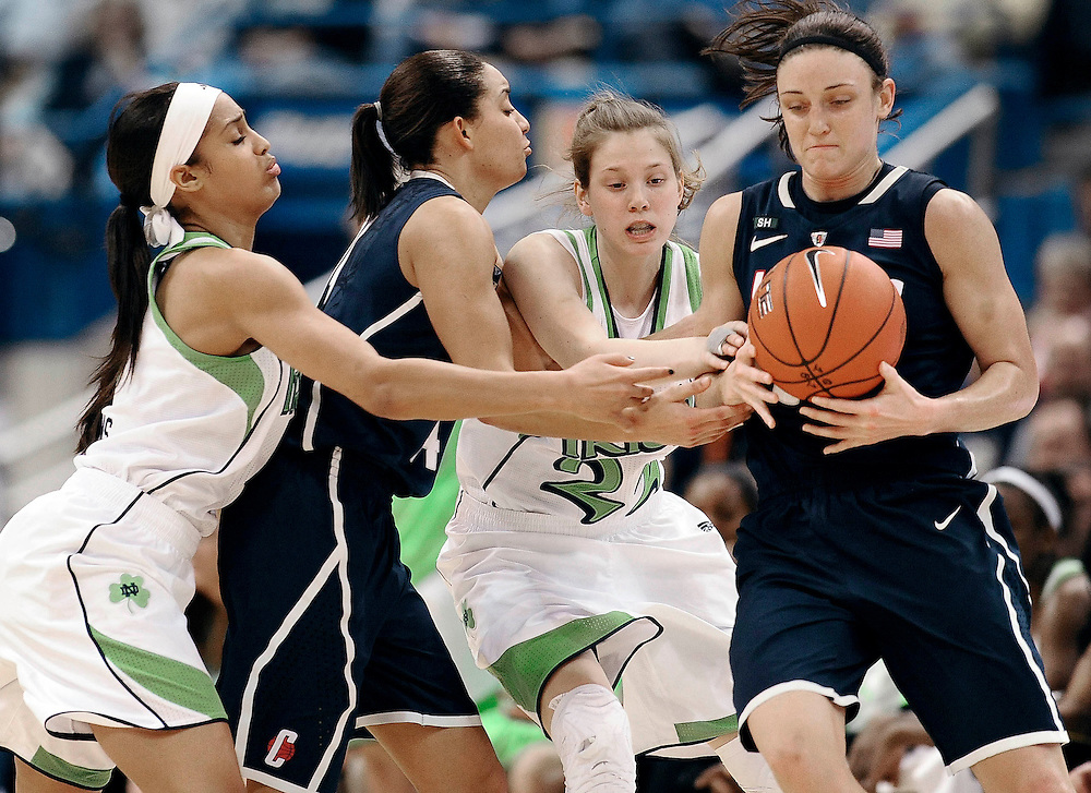 Connecticut's Bria Hartley, second from left,  is pressured by Notre Dame's Skylar Diggins, left, and Notre Dame's Madison Cable, second from right, as she passes the ball to Connecticut's Kelly Faris, right, in the first half of an NCAA college basketball game in the final of the Big East Conference women's tournament in Hartford, Conn., Tuesday, March 12, 2013. (AP Photo/Jessica Hill)