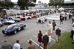 © licensed to London News Pictures. 12/09/2015<br /> Goodwood Revival Weekend, Goodwood, West Sussex. UK.<br /> The Goodwood Revival is the world's largest historic motor racing event. Competitors and enthusiasts dress in period fashions recreating the glorious days of the race circuit.<br /> Pictured. Classic cars leave the paddock at the start of the race.<br /> <br /> Photo credit : Ian Whittaker/LNP