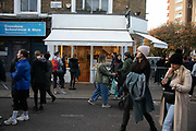 Broadway Market teeming with people during the second coronavirus national lockdown on November 7th 2020 Hackney, East London, United Kingdom. Saturday is market day in Hackney and the streets are busy with people shopping, eating, drinking and enjoying the good weather in-spite of the national lockdown. The UK Government introduced a 4 week lockdown from November 5th - December 2nd to combat the coronavirus outbreak. It is the third day of the national lockdown and restrictions mean that people are only allowed to meet outside, in pairs and only if keeping social distance. Only if they already live together or have formed a social bubble can they interact freely.