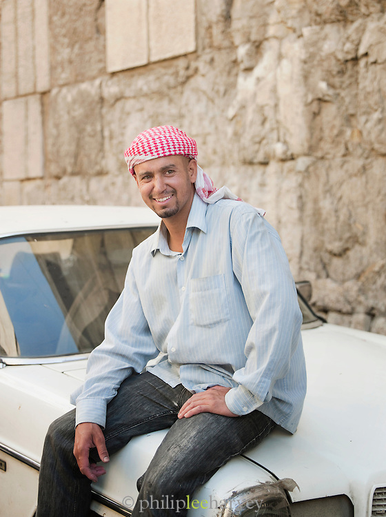 A man sits on his car in the Old City in Damascus, Syria