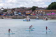 Four people on Stand Up Paddle Boards paddle past Folkestone Harbour back into Sunny Sands beach in Folkestone, Kent, England, United Kingdom.  The trawler boats in the background are decorated are preparing for the annual Trawler race and fun day and the crowds have gathered to watch on the harbour side.