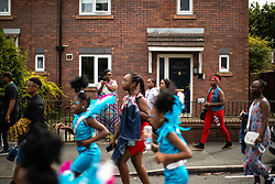 © Licensed to London News Pictures . 11/08/2018. Manchester , UK . A woman stands on a driveway and records the procession as is passes through Moss Side . The annual Moss Side Caribbean Carnival procession , celebrating dance , music and Afro-Caribbean culture , which passes in a loop from Alexandra Park and through the streets of Moss Side . Photo credit : Joel Goodman/LNP