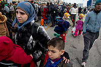 ATHENS, GREECE - FEBRUARY 04: A Syrian mother holds her two sons after arriving at the Pireaus port by ferry from the Greek Islands on February 04, 2016 in Athens, Greece. After arriving, refugees are distributed amongst the different gates of the port; one of the gates has been converted into an informal warehouse of food, clothing, medicine and other essentials, which are then distributed to the refugees and migrants in the port by volunteers. Photo: © Omar Havana. All Rights Are Reserved