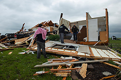 Jacob Boatwright, 14, left, watches while friends and neighbors helped clear items from his home west of Bonner Springs, Kansas after it was hit by a tornado Tuesday night, May 29, 2019. Jacob rode out the storm with his parents Travis and Kay Boatwright in the basement of the home and had to crawl out on their hands and knees. They escaped unharmed. Photo byChris Ochsner/Kansas City Star/TNS/ABACAPRESS.COM