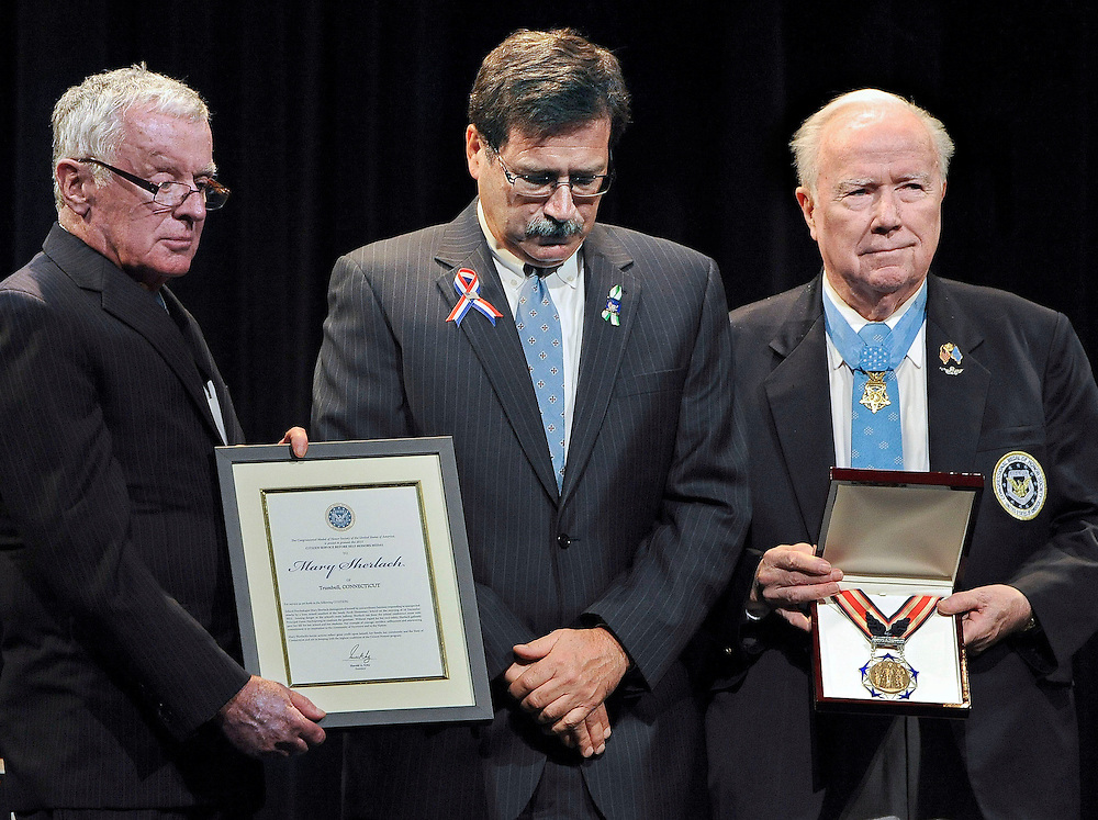 William Sherlach, second from right, accepts the citizen honor of the Congressional Medal of Honor, from Medal of Honor Recipient presenters Paul Bucha, left, Thomas Kelley, second from left, and Bruce Crandall, right, on behalf of his late wife Mary Sherlach in Newtown, Conn., Monday, May 6, 2013. The Congressional Medal of Honor Society says Rachel D'Avino, Dawn Hochsprung, Anne Marie Murphy, Lauren Rousseau, Mary Sherlach and Victoria Soto exemplified courage, sacrifice and selflessness in trying to protect students from the gunman at Sandy Hook Elementary School. (AP Photo/Jessica Hill)