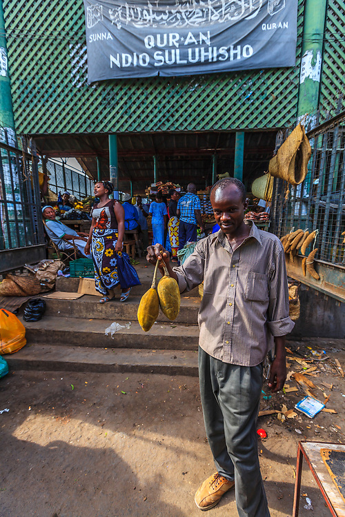 A seller offers baobab fruits in Mackinnon Market in Mombasa, Kenya. The fruit has a velvety shell and is about the size of a coconut, weighing about 1.44 kilograms (3.2 lb). It has a tart and acidic flavor, described as somewhere between grapefruit, pear, and vanilla.