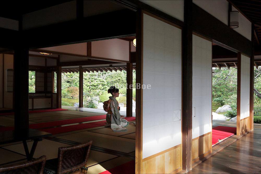 young woman in kimono sitting on tatami floor in a traditional Japanese house with garden