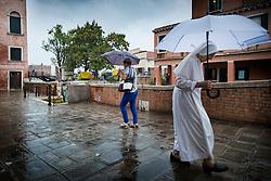 A nun uses an umbrella to shelter from a shower of rain as she walks through Dorsoduro, Venice, Italy.<br /> Photo: Ed Maynard<br /> 07976 239803<br /> www.edmaynard.com