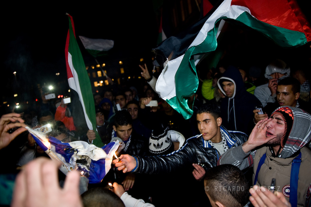 22.11.12. Copenhagen, Denmark.  Support Gaza protest demonstration in solidarity with the Palestinian people in front of the Danish Parliament. A protester burns a flag of the Israeli regime during a demonstration.Photo: © Ricardo Ramirez