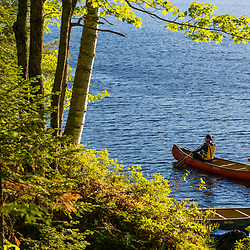 Two women paddling a canoe in the morning on Silver Lake in Piscataquis County, Maine. Near Greenville.