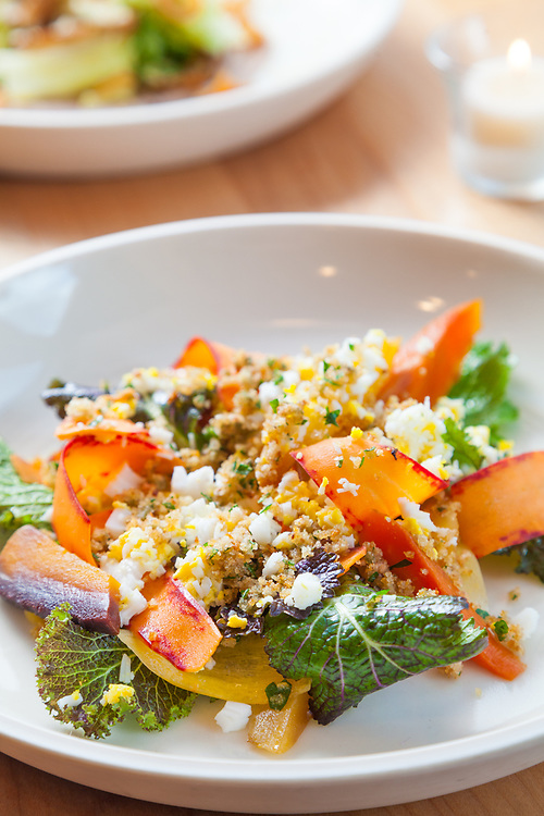 Roasted and raw carrots with peppery mustard greens, caper berries, a sieved duck egg and rosemary breadcrumbs. In the background is Roasted sun chokes with sugarloaf chicory, pear walnut butter and cognac vinaigrette. photographed at Coquine in Portland.