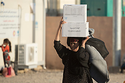 Licensed to London News Pictures. 22/10/2016. A female Iraqi refugee carries boxes of supplies on her head at the Dibaga refugee camp near Makhmur, Iraq.<br />