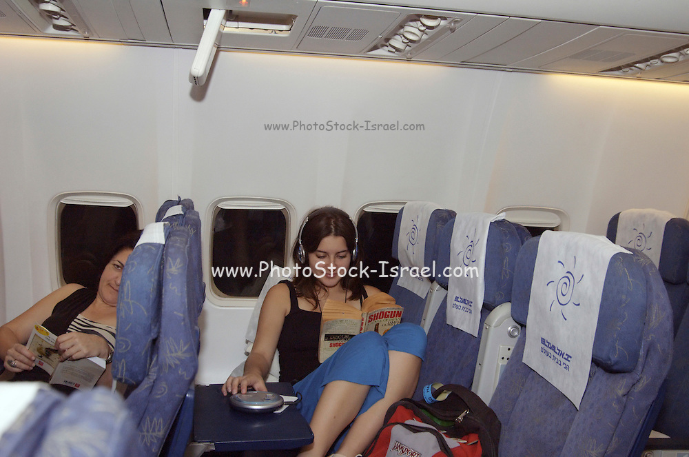Woman and teenager Travellers resting during an El Al flight on a Boeing 767, July 2006, Model released