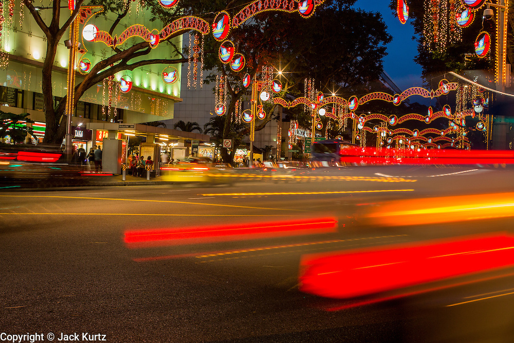 """22 DECEMBER 2012 - SINGAPORE, SINGAPORE:  Traffic goes under Christmas lights on Orchard Road during """"Christmas on a Great Street"""" in Singapore. Businesses on Orchard Road, Singapore's famed shopping street, sponsors the annual event. The street is decorated with holiday lights, stores stay open late and crowds pack the area. This is the 8th year Singapore has held the """"Christmas on a Great Street"""" event.   PHOTO BY JACK KURTZ"""