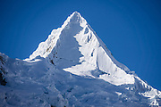 The icy pyramid of Nevado Alpamayo (19,511 ft or 5947 m) is seen from Alpamayo Valley, in the Cordillera Blanca, Andes Mountains, Peru, South America. Day 7 of 10 days trekking around Alpamayo, in Huascaran National Park (UNESCO World Heritage Site).