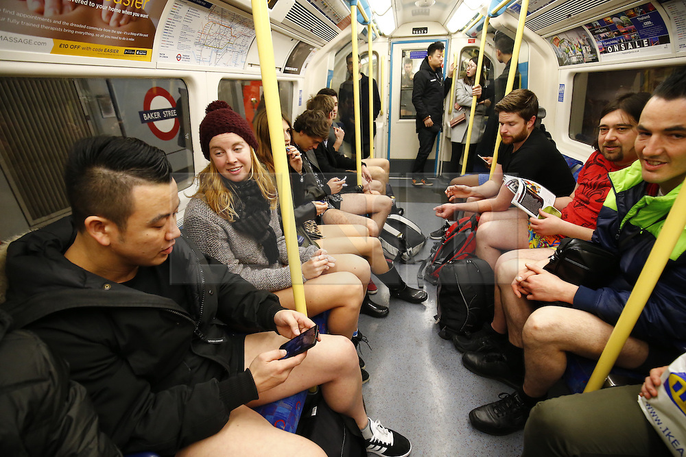 © Licensed to London News Pictures. 10/01/2016. London, UK. People take part in the annual 'No Trousers Tube Ride' event on the London Underground on Sunday, 10 January, 2016. Participants travel on the tube without trousers as part of the event to surprise other passengers. The tradition started by a collective called 'Improv Everywhere' in New York 14 years ago. Photo credit: Tolga Akmen/LNP