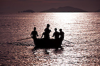 Traditional coracle fishing boat silhouetted in the early morning light off China beach in Vietnam.