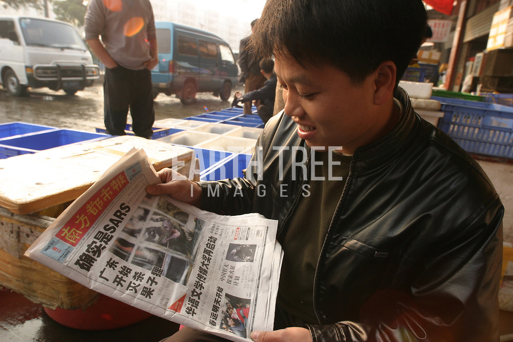 A man reads about SARS virus, in China. After people consumed wildlife and civit cats at many of the local wildlife markets and restaurants in China. Severe acute respiratory syndrome (SARS) is a viral respiratory disease of zoonotic origin caused by the SARS coronavirus (SARS-CoV). Between November 2002 and July 2003, an outbreak of SARS in southern China caused an eventual 8,098 cases, resulting in 774 deaths reported in 37 countries, with the majority of cases in China (9.6% fatality rate) according to the World Health Organization (WHO). Photo: Paul Hilton / Earth Tree Images