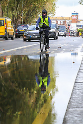© Licensed to London News Pictures. 25/09/2019. London, UK. A cyclist avoids the flood on Green Lanes in north London caused by heavy overnight downpour. Photo credit: Dinendra Haria/LNP