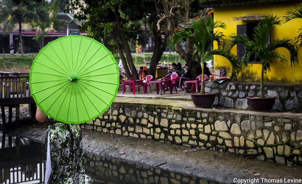 Lady with bright green umbrella off to the side with typical hoi an yellow wall and background. Vietnam