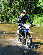 Dirk Mathews rides his Suzuki DRZ-400S motorcyle up a stream in Arkansas.