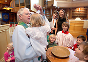 Father Ken Asel performs his last baptism at St. John's Episcopal Church with 18-month-old Reese Freed, daughter of Vance and Greer Freed. Other children in the congregation are invited to the front where they  can more easily see the ceremony.