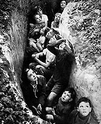 Battle of Britain July 1940-May 1941: Children sheltering in a trench in hopfields in Kent, 3 September 1940, while Royal Air Force fighters engage with Luftwaffe (German Air Force) bombers on their way to bomb London.