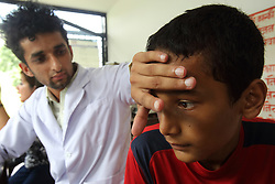 Health Worker Jiban Poudel talks with Vivek Sunarvisit, a school boy who is visiting the clinic in this temporary location while a new clinic is being built. Batulechaur Health Post, Pokhara, Nepal