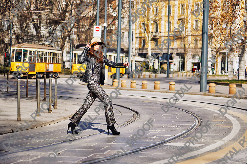 Model crossing the street with cable cars (Trams) at the background in Milan Italy during the day