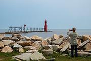 A woman takes a photograph of the Algoma Lighthouse, Algoma, Wisconsin, USA.