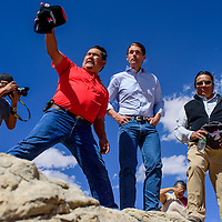 Gilbert Dayzie of the Navajo Abandon Mine Land Reclamation department, points out uranium sites on the landscape for Sen. Martin Heinrich, center, during a tour in Red Valley Friday.