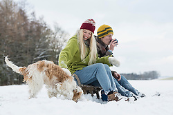 Young couple sitting on Sledge with dog in snowy landscape during winter, Bavaria, Germany